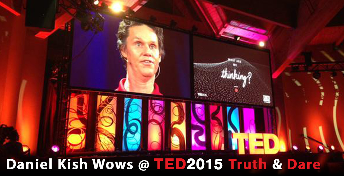 "A photo banner shows Daniel Kish, President of World Access For The Blind, projected on a large screen as he rehearses for his session called ""What Are We Thinking"", which is depicted as a graphic on another large screen beside him. Both are suspended over a multi-colored, multi-panel light installation at TED2015 in Vancouver. The headline reads: Daniel Kish Wows at TED2015 Truth & Dare."
